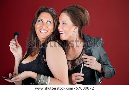 Two giggling cougars dressed in black prepare their makeup - stock photo