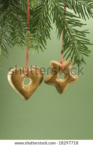 Two gingerbread cookies hanging under fir branch and isolated against green paper - stock photo