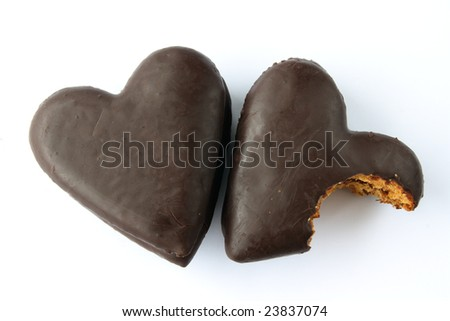 Two gingerbread hearts covered with chocolate with jam filling, one partially bitten. - stock photo