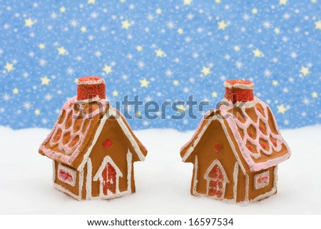 Two gingerbread houses on snow with star background, gingerbread house - stock photo