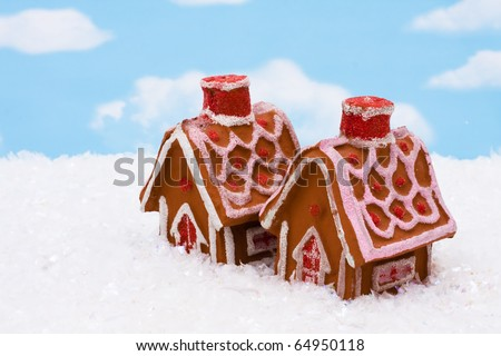 Two gingerbread houses sitting on snow with a sky background, gingerbread houses - stock photo