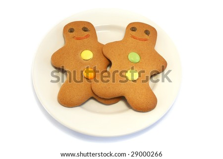 Two Gingerbread men on a cream plate on a white background - stock photo