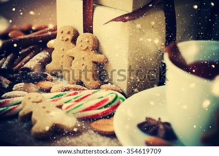 Two Gingerbread Men with Christmas Presents and Festive Spices on Table. Toned. Drawn Falling Snow - stock photo