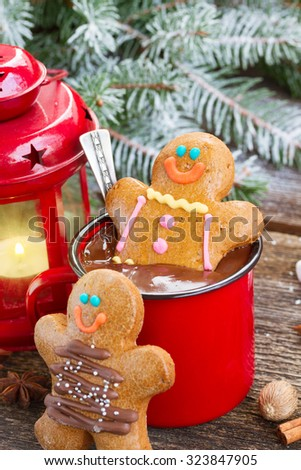 two  Gingerbread men with mug of  chocolate and glowing lantern on wood - stock photo