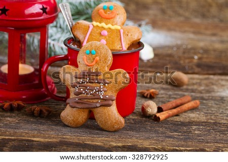 two  Gingerbread men with mug of  chocolate and red lantern on wood - stock photo