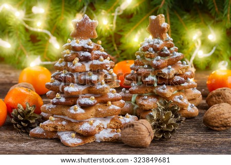 two gingerbread  tree with tangerines and christmas lights in background - stock photo