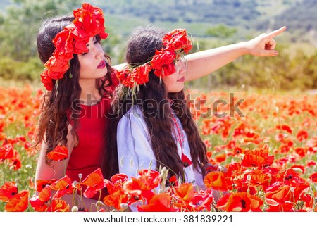 Two girl are looking around in poppy field