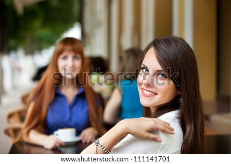 two girl friends drinking coffee at breakfast or dinner at an outdoor cafe - stock photo
