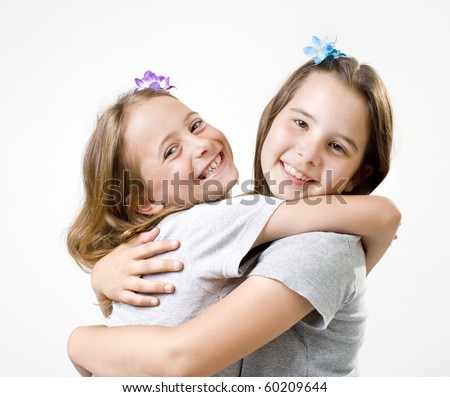 two girl friends embrace isolated on white - stock photo