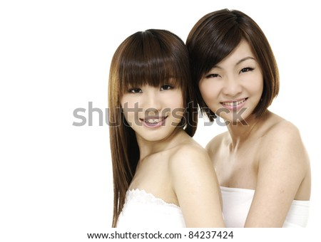 Two girl friends in bath dress together smiling - stock photo