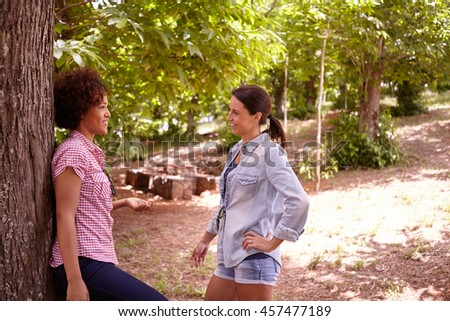 Two girl friends laughing and chatting in the dappled afternoon sunshine while one leans against a tree wearing casual clothing