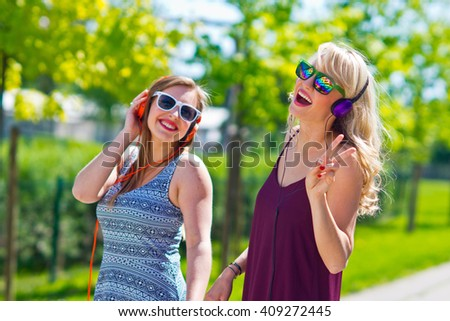 Two girl friends listen music and having fun