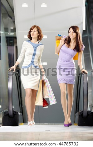 Two girl-friends on shopping has risen on the escalator with bags - stock photo