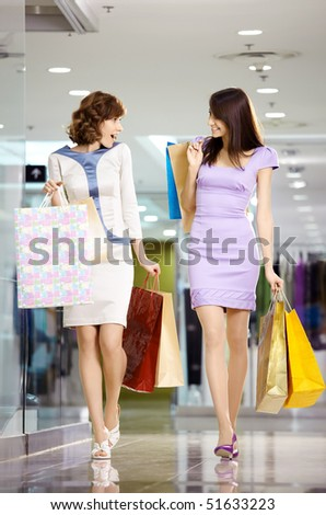 Two girl-friends on shopping walk on shopping centre with bags - stock photo