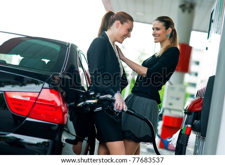 two girl friends refuel car and having fun on gas station