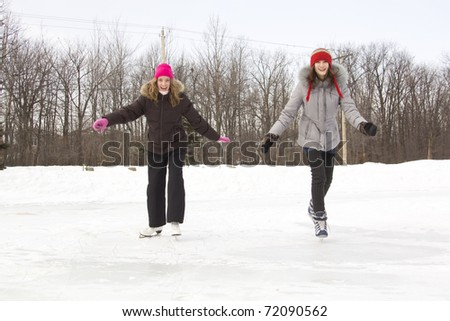 Two girl friends skating on a lake together during winter season - stock photo