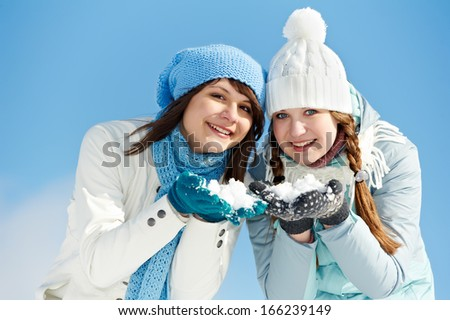 Two girl having fun with snow in winter outdoors - stock photo