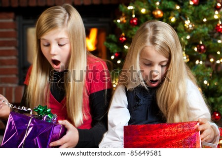 two girl holding gifts and are surprised - stock photo