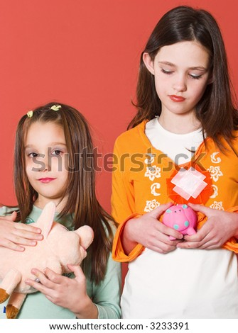Two girl holding they're toy banks - stock photo