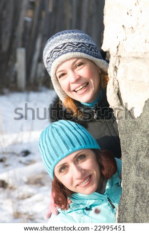 Two girl looks out from round the corner - stock photo