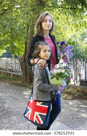 Two girl of different ages flowers on the street - stock photo