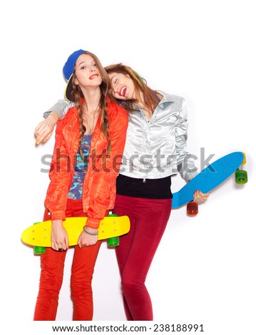 Two girl skaters go crazy and have fun together.  Beautiful sporty women Emotion.  White background, not isolated - stock photo