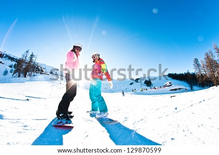 two girl snowboarders having fun - stock photo