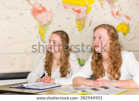Two girl  students in geography class with  world chart - stock photo