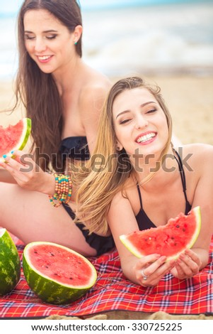 Two girlfriend resting on the summer beach  - stock photo