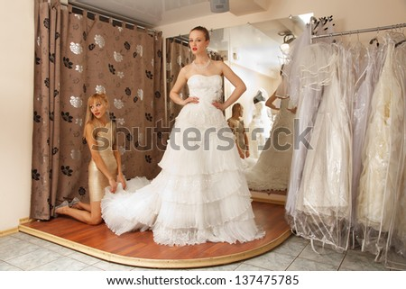 Two girlfriends  - A Bride-To-Be and  bridesmaid Trying On A Wedding dress - stock photo
