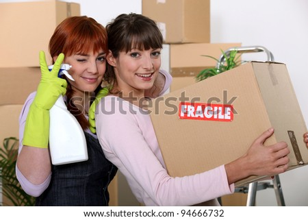 two girlfriends arranging their new apartment - stock photo