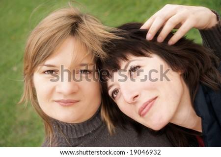 two girlfriends blonde & brunette double portrait - stock photo