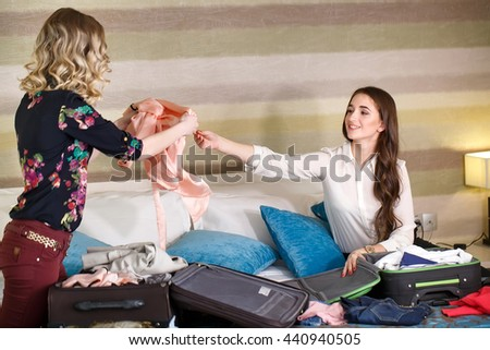 Two Girlfriends collect a suitcase in a hotel room.