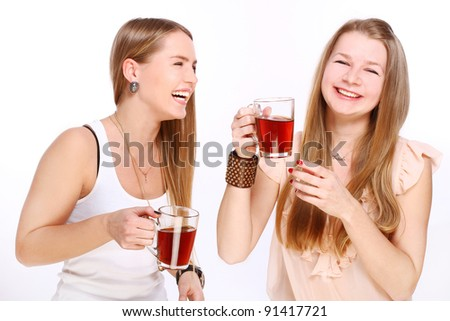 Two girlfriends drinking tea isolated over white - stock photo