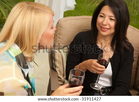 Two Girlfriends Enjoy Wine on the Outdoor Patio. - stock photo