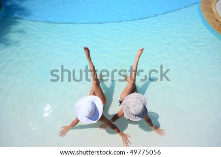 Two girlfriends enjoying the sun in a swimming pool on vacation or holiday - stock photo