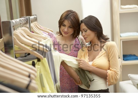 Two girlfriends examining garments in fashion store. - stock photo