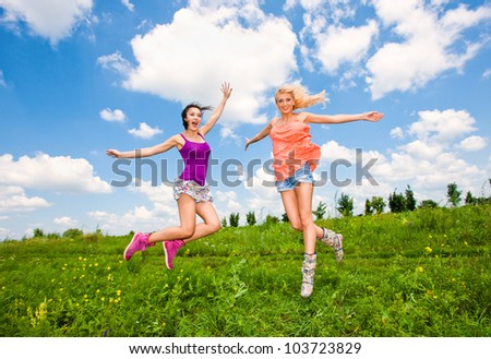 two girlfriends having fun in blue sky - stock photo