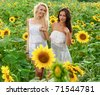 two girlfriends having fun in field of sunflowers - stock photo