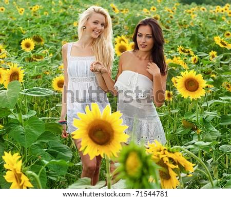 two girlfriends having fun in field of sunflowers - stock photo