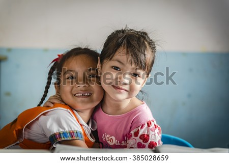 Two girlfriends hugging each other - stock photo