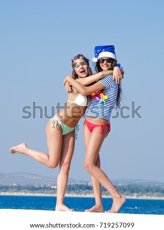 Two girlfriends in a Santa hat and in the image of a pirate during a beach holiday?.
