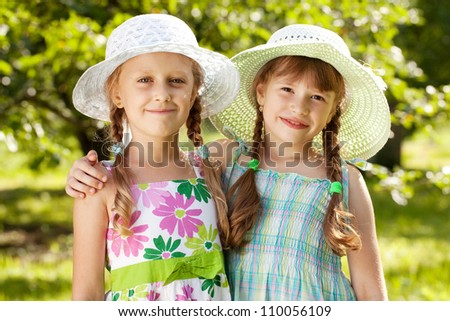 Two girlfriends in hats and summer dresses