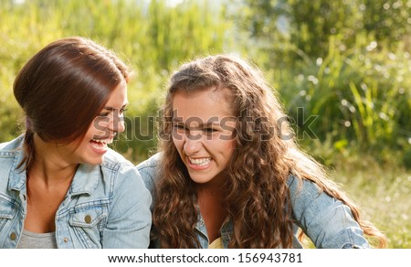two girlfriends in jeans wear outdoors sitting  laughing - stock photo