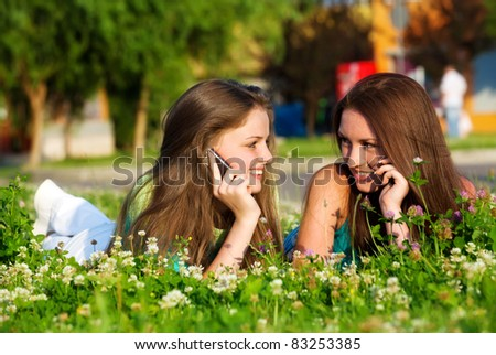 Two girlfriends in park with a mobile phone - stock photo