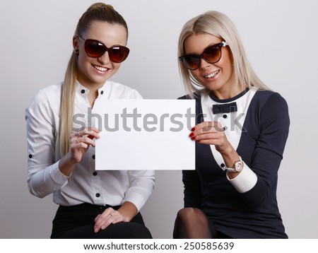 Two girlfriends in sunglasses looking ahead while holding a blank sheet of paper together - stock photo