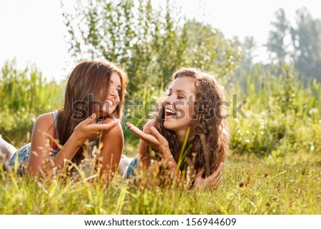 two girlfriends in T-shirts  lying down on grass talking having good time