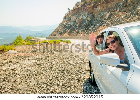 two girlfriends in the passenger seat in a car traveling - stock photo