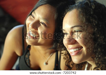 Two girlfriends laughing and having fun; shallow depth of field and natural light - stock photo