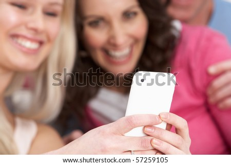 Two Girlfriends Looking At Pictures On phone At Home - stock photo